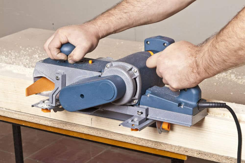 Man using an electric hand planer