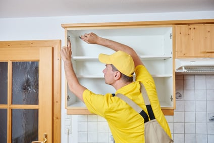 Man making sure cabinet fits while installing