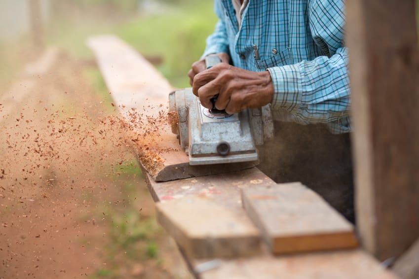 carpenter using an electric planer on a wooden plank outside