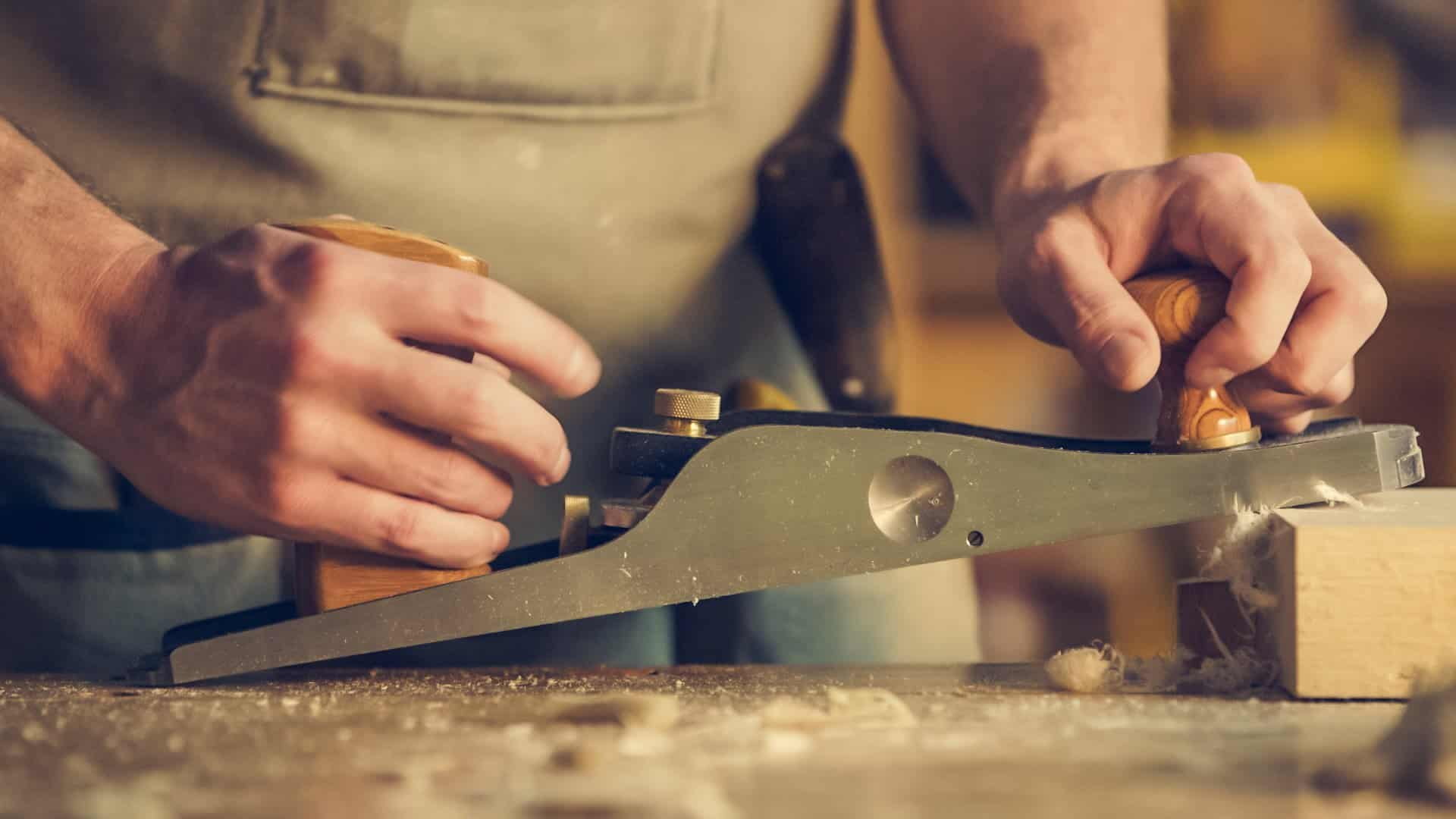 Photo of a man with a large old manual hand plane