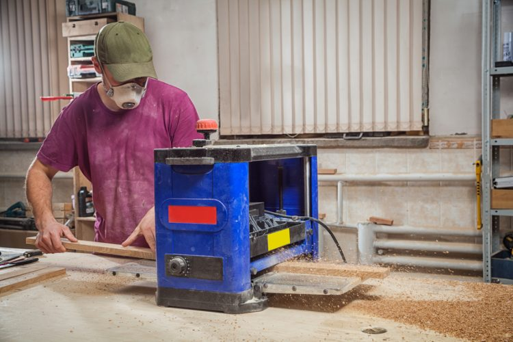 Man Using a Blue Thickness planer